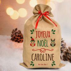 Découvrez la Ho! Ho! Hotte de Noël d'A-qui-S , le joli sac personnalisé en toile de jute, sorti tout droit de l'atelier des lutins d'A-qui-S ! Pour mettre une touche de magie supplémentaire à cette fête et faire rêver les petits comme les grands, vous pourrez y glisser vos cadeaux et le déposer (discrètement) sous le sapin le jour J. Vous pouvez personnaliser votre sac et choisir son décor parmi 5 thèmes différents.  100% fabriqué en toile de jute, il est livré avec son ruban en satin…