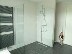Inloopdouche met muurtje als aansluiting tegen het bad op het