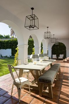 Chic covered patio with arched doorways boasts a tow of iron and glass lanterns illuminating a concrete and wood outdoor dining table lined with white Tolix Chairs and a sawhorse bench atop a terracotta floor.