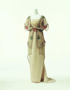 1910 - Vestido de Paul Poiret - Vestido de noite de cetim com uma faixa de tule dourado na cintura e um sobrevestido de tule com bordados e fios de ouro. (Cally Blackman - 100 Years of Fashion)