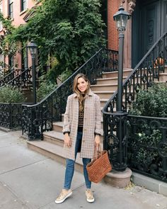 Julia Engel shares her daily look on Gal Meets Glam. Julia is wearing an A.P.C. coat, Demylee sweater, Frame jeans, and Converse sneakers.