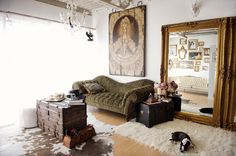 A cowhide rug, oversize gold mirror and vintage trunk complete this seating area