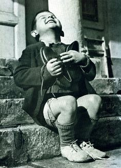 Six year old orphan from Austria ecstatically embraces a new pair of shoes just given to him by the Red Cross. Photo: Gerald Waller, 1946.