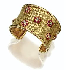 14 KARAT GOLD, RUBY AND DIAMOND BANGLE-BRACELET, VAN CLEEF & ARPELS, NEW YORK, 1942 The open-ended cuff of basketweave design decorated with florets and trefoils of round rubies and round diamonds, the edges studded with small round rubies within engraved 'stars', signed Van Cleef & Arpels NY, numbered 3015, 1 ruby missing.