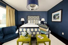Yellow and blue bedroom features walls clad in navy textured wallpaper lined with bed with headboard and footboard upholstered in blue and gold hex fabric flanked by dark wood nightstands topped with navy gourd lamps with lucite bases by Robert Abbey illuminated by  blue vinyl drum pendant hanging over a pair of olive green lacquer tables placed at the foot of the bed.