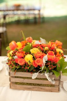 orange and yellow arrangement of spray roses, tulips and dahlias