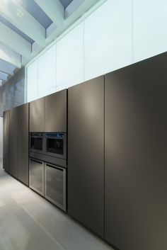 This industrial loft kitchen gets a modern, contemporary design with FENIX NTM matte surfaces.