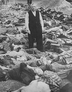 Commandant of the concentration camp Kaufering IV, SS officer Eichelsdörfer, stands among the killed prisoners in his camp after liberation.