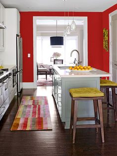 """The paint finish you choose will convey the attitude of the color itself. """"If you want to go all the way, go for high-gloss -- the room will feel like a jewel box,""""designer Molly Luetkemeyer says. """"A matte or flat finish will be more chalky and subtle."""" Tomato Red in This Space: In this kitchen, a matte tomato red introduces color without being overwhelming, and the green plays out on the island, while the yellow is picked up in the stool cushions./"""