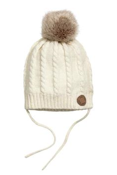Cable-knit hat: Cable-knit hat in a soft cotton blend containing some wool with a faux fur pompom on the top and ties under the chin. Jersey lining.