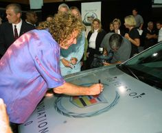 Robert Plant signs the hood of a 2003 Cadillac CTS at the General Motors world headquarters August 22, 2002 in Detroit, Michigan.
