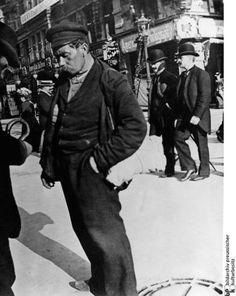 Heinrich Zille-Fotos:  Straßenszene:  Erschöpfter Mann mit Schiebermütze, aufgenommen 1900.