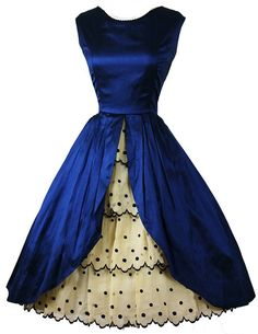 1950's cocktail party dress in cobalt silk satin, with embroidered ruffle organza skirt, fitted bodice, petal front open silk skirt, and embroidered organza ruffles embellished underskirt. No maker label.