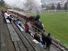 Kereta Melintasi Kursi Penonton Stadion. Slovakian soccer fans' view of game obstructed by a whole train passing through.