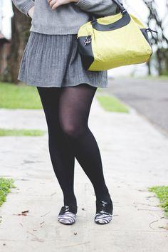 Look com peças neutras em tons de cinza composto por saia suéter oxford de zebrinha (animal print) e bolsa amarela da Kipling
