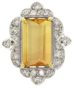 Precious topaz and diamond cluster ring, circa 1950. A yellow gold and platinum ring set with one central rectangular emerald-cut precious topaz in a yellow gold claw setting with an approximate weight of 4.50 carats, encircled by a scalloped border of twenty three round brilliant cut diamonds in platinum millegrain bead settings, above an openwork gallery, flanked by tri-part shoulders set with six round brilliant cut diamonds in platinum millegrain settings. Berganza.
