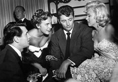 Rock Hudson, Terry Moore, Robert Mitchum and Marilyn Monroe at the home of director Jean Negulesco celebrating the premiere of How to Marry a Millionaire