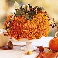 For this great centerpiece you will need orange flowers, skewers, floral foam, pumpkin stem, and leaves. Soak your floral foam until satura...