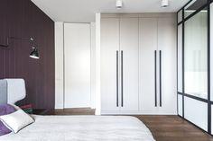 Sypialnia w mokotowskim mieszkaniu, szklana ściana oddzielająca łazienkę prywatną, bakłażanowa boazeria, łóżko-uszak w filcowej tapicerce. Projekt: Borysewicz i Munzar