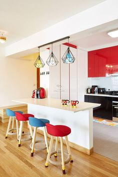 A colourful breakfast bar counter serves as a divider for the kitchen.