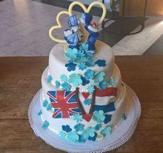 Zeer mooie gestapelde bruidstaart, Hier is er een samensmelting van het Verenigd Koninkrijk en Nederland, door middel van de nationale vlaggen!  Bovenop de mooie Chocolade harten met daarvoor een karakteristiek delfts blauw paartje!