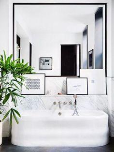 marble half wall behind a freestanding tub.