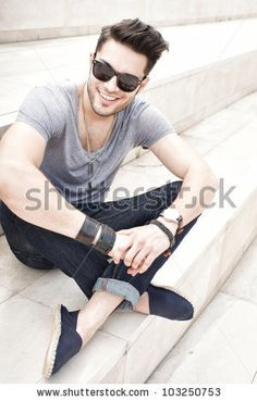 handsome male fashion model smiling, dressed casual - outdoor - stock photo