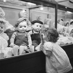 Child enchanted with dolls at Macy's, New York, 1949. Super sweet!
