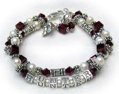 This is a July Birthstone Crystal Bracelet with July Crystals. It has 1 name string and 1 blank string. It is shown with 3 add-ons; Baby Boy Bootie Charm, 2 Birthstone Crystal Charms. It is also shown with a sterling silver lobster claw clasp. Item: DBLSS5-2