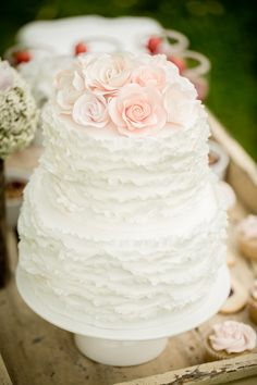 Beautiful pale pink roses atop this white ruffled cake