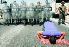 A Palestinian man carries on with his salaah (shalat) undeterred by the amount of IDF amassed behind him.