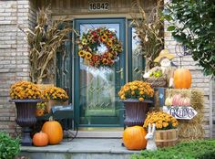 Beautifully decorated entry with dried corn stalks, urns filled with mums, bale of hay, pumpkins and baskets. Top it all off with a gorgeous flower wreath on the door. That's how to greet Autumn!
