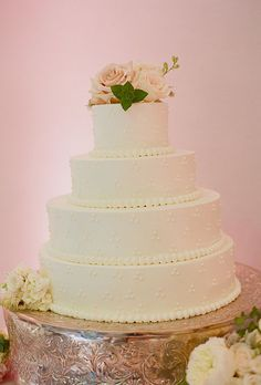 Round, white four-tier wedding cake with pink roses as toppers by Design Cuisine (Photo: Kate Headley)