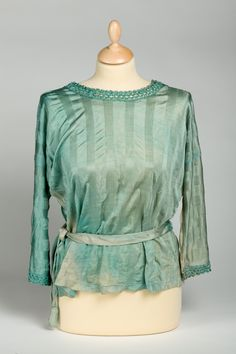 Blouse ca 1923  A pale kingfisher blue rayon stockinette blouse decorated with crochet at neck and on sleeve ends.