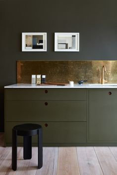 From Norfolk, England, brand Naked Kitchens, this dark green kitchen from the Ladbroke line has marble and walnut countertops with a bronze backsplash. Photograph courtesy of Naked Kitchens.