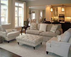 Neutral living room with overstuffed beige sofa, beige linen armchairs and a tufted ottoman