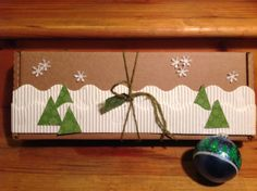 Snow and Snowflake Gift Wrap - Recycled box, recycled bulletin board trim or corrugated cardboard ribbon, trees are from cardboard from an ornament I brought last year. http://www.pinterest.com/bethob/wrap-it-up-with-a-little-whimsy/Snowflakes punched from shiny book jacket.