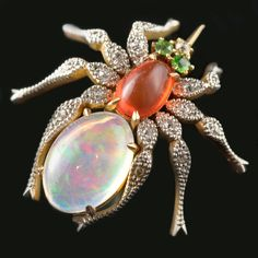 Unusual multi-gem spider brooch the body set with a cabochon opal and fire opal with demantoid garnet and diamond highlights and eight diamond set legs.  Period:  Victorian c1900  Origin:  European