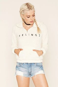 """A knit faux fur hoodie featuring a """"Feelings"""" embroidery, an oversized drawstring hood, zipper front, kangaroo pocket, and long sleeves with ribbed cuffs. #thelatest"""