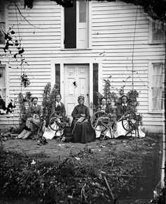 Siri Rustebakke, center, sits in front of a house with her daughters and daughter-in-law and four spinning wheels, 1873.