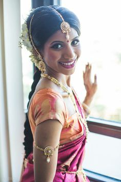 Beautiful Bride in a Magenta Silk Saree and Orange Blouse with Gold Jewelry and Flowers