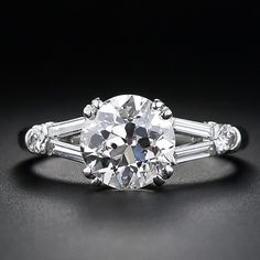 2.01 carat European cut, platinum. I1 clarity, K color. Accented with 2 Round Brilliant and 4 Baguette cut diamonds. 2.26 total weight.
