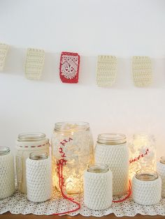 A cluster of jars in knitted jackets -- loose knitting lets the light from tea lights shine through