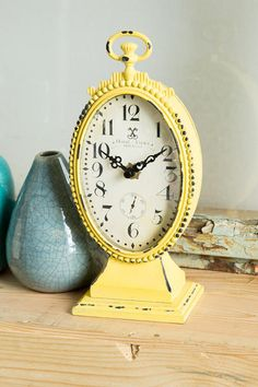 """Don't be late for your important date! Decorate your apartment, home, or office with this beautiful, vintage-inspired yellow clock! Pair with our additionalhome decor options to complete your room.<br /> <br /> - 10.5"""" height<br /> -Yellow finish<br /> - Material: metal<br /> - By Creative Co-op<br /> - Imported<br />"""