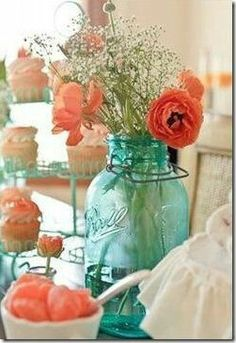 Turquoise bottles with salmon coloured flowers are great with the white centrepieces of the tables