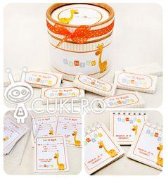Caja circular forrada con mini chocolates de souvenir, tarjetas de recuerdo para completar con los datos del bebé el día de su nacimiento y anotadores de souvenir.