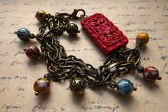 Bracelet made with Chinese cloisonne beads, brass chain and faux cinnabar.