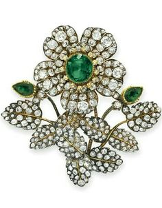 AN EMERALD AND DIAMOND BROOCH. Designed as an old mine-cut diamond flower blossom, set with an oval-cut emerald pistil and rose-cut diamond stamen, extending a spray of old mine-cut diamond leaves with two pear-shaped emerald buds, mounted in gold and silver