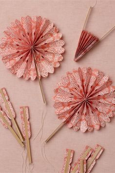 """Crinkle Fans (10) from www.BHLDN.com   Style: 25570177  A muted coral motif sprinkled over Lokta paper to kick up a breeze or to add a pinwheeling flair to tabletops or floral arrangements.        Set of 10      7""""L, 8""""diameter      Lokta paper, bamboo, cotton string      Handmade in Nepal      Exclusive to BHLDN"""