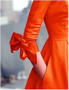 Pretty orange dress with bow detail at the elbow. I wish I knew where to find this!